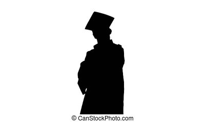 Silhouette Proud male student in graduation gown posing with...