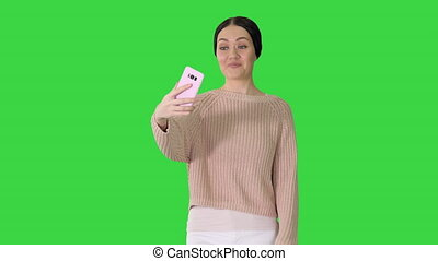 Medium shot. Front view. Smiling and gesturing young woman having video call on her phone while walking on a Green Screen, Chroma Key. Professional shot in 4K resolution. 043. You can use it e.g. in your medical, commercial video, business, presentation, broadcast