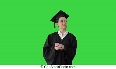 Medium shot. Front view. Smiling female graduate in mortarboard sharing happy news on her phone while walking on a Green Screen, Chroma Key. Professional shot in 4K resolution. 043. You can use it e.g. in your medical, commercial video, business, presentation, broadcast