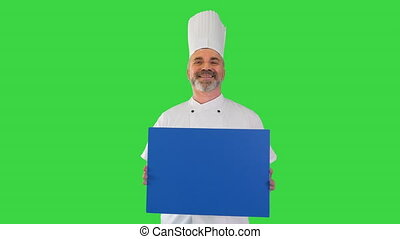 Medium shot. Front view. Smiling male chef cook holding blank board on a Green Screen, Chroma Key. Professional shot in 4K resolution. 059. You can use it e.g. in your medical, commercial video, business, presentation, broadcast