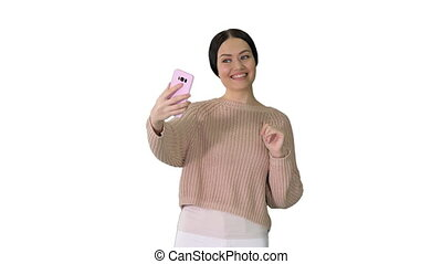 Medium shot. Front view. Smiling young woman having video call on her phone waving hand on white background. Professional shot in 4K resolution. 043. You can use it e.g. in your medical, commercial video, business, presentation, broadcast