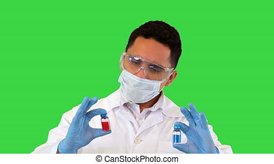 Medium shot. Front view. The doctor looking at the two new vaccines in ampoules and makes a choice showing the red one to camera on a Green Screen, Chroma Key. Professional shot in 4K resolution. 070. You can use it e.g. in your medical, commercial video, business, presentation, broadcast