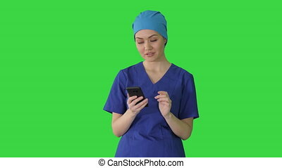 Thinking female doctor using her smartphone on a Green Screen, Chroma Key.