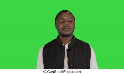 Medium shot. Front view. Very happy afro American showing thumb up on a Green Screen, Chroma Key. Professional shot in 4K resolution. 065. You can use it e.g. in your medical, commercial video, business, presentation, broadcast