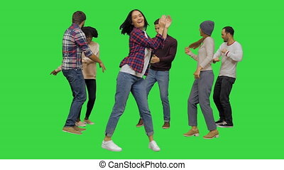 Medium shot. Front view. Young lively beautiful girl dancing with the others at the party on a Green Screen, Chroma Key. Professional shot in 4K resolution. 042. You can use it e.g. in your medical, commercial video, business, presentation, broadcast