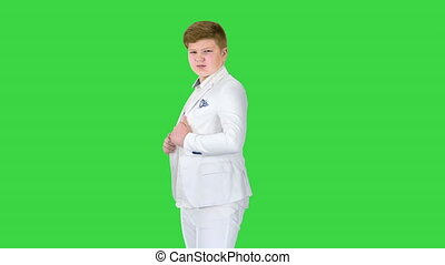 Young teenager boy in a business suit stands at the mirror on a Green Screen, Chroma Key.
