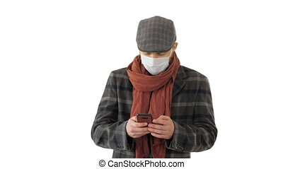 Gentleman in medical mask using phone and walking on white background.