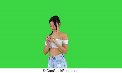 Girl dancing and aswering the call on the phone on a Green...