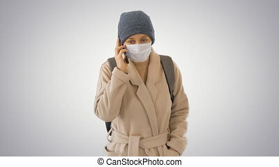 Girl in a protective mask walking and making a call on the phone on gradient background.