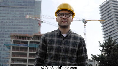 Handsome architect man wearing hard hat walking from ...