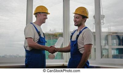 Handsome construction workers in protective helmets shaking hands.