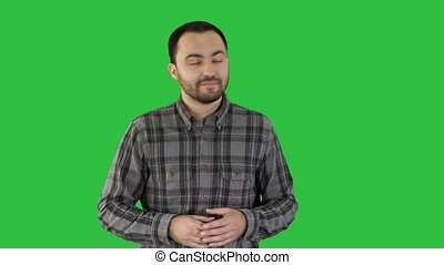 Handsome young man walking and looking to the camera and pointing to the sides showing something on a Green Screen, Chroma Key.