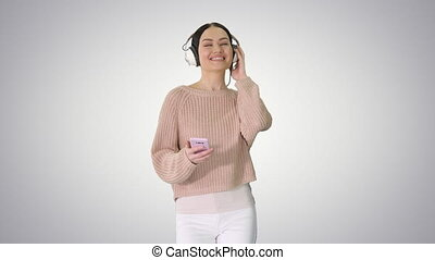 Happy girl walking listening to music with smart phone wearing headphones on gradient background.