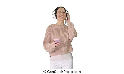 Happy girl walking listening to music with smart phone wearing headphones on white background.