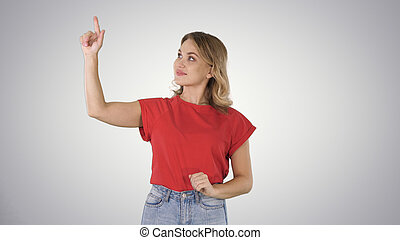 Happy young woman showing a product pointing with her finger to sides Presentation on gradient background.