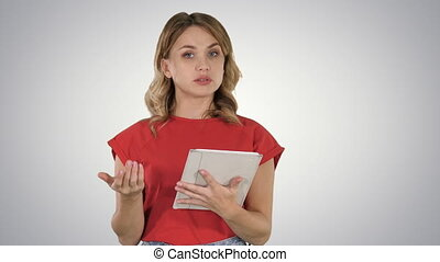 Lady wearing red t-shirt holding a tablet in her hands with a serious face talking to camera on gradient background.