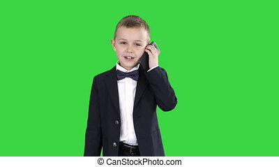 Little boy in a costume making a phone call while walking on a Green Screen, Chroma Key.