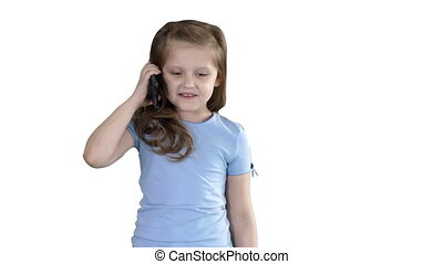 Little schoolgirl making a call with a smartphone while walking on white background.
