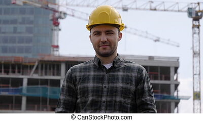 Male Construction Worker On Building Site Wearing Hard Hat.