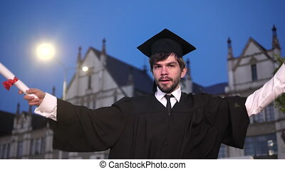 Male graduate dancing in academic.