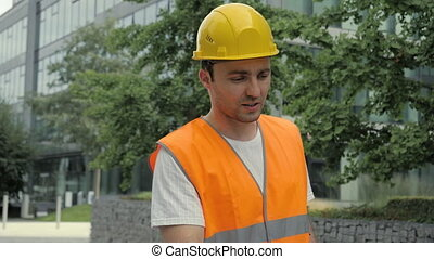 Male Industrial Engineer in Hard Hat and Safety Jacket Walking Along Modern Buildings and Talking to Camera.