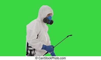 Medium shot. Man in a hazmat suit walking and spraing with a disinfectant on a Green Screen, Chroma Key. Professional shot in 4K resolution. 53. You can use it e.g. in your medical, commercial video, business, presentation, broadcast