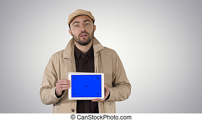 Man in trench walking and holding tablet with blue screen mockup presenting something on gradient background.