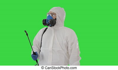 Man wearing an personal protective equipment suit, gloves, mask, and face shield ready to disinfect on a Green Screen, Chroma Key.