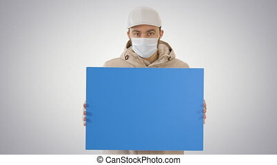 Casual man with copy space billboard wearing protective mask on gradient background.