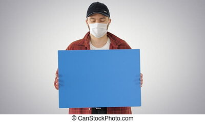 Medium shot. Mockup blue screen. Mature Male Farmer In Medical Mask Holding Blank Placard on gradient background. Professional shot in 4K resolution. 53. You can use it e.g. in your medical, commercial video, business, presentation, broadcast