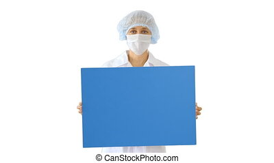 Woman doctor in a mask holding an empty board on white background.