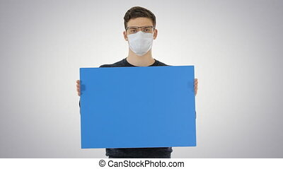 Medium shot. Mockup blue screen. Young man in medical mask showing and displaying placard on gradient background. Professional shot in 4K resolution. 53. You can use it e.g. in your medical, commercial video, business, presentation, broadcast