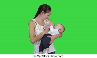 Mother gives baby to drink from bottle on a Green Screen, Chroma Key.