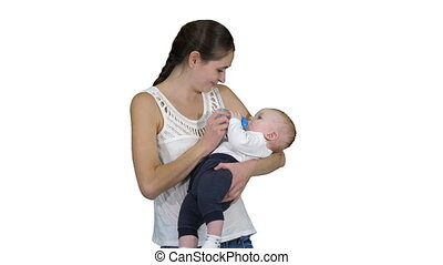 Mother gives baby to drink from bottle on white background.