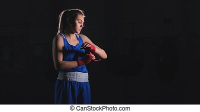 Medium shot of a beautiful athletic female boxer pulls red...