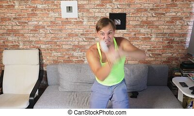 Medium shot of a man dancing to video game. in a home...