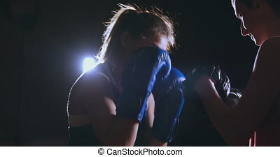 Medium shot of beautiful fitness woman boxer treneruemsya...