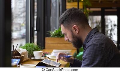 Medium shot of guy and a girl discuss their startup with a tablet sitting in a cafe