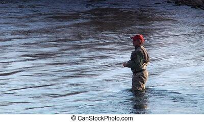 medium shot  of man flyfishing in River in wintertime