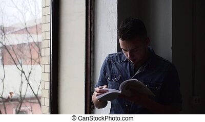 Medium shot of man reading book in dark room standing by the window