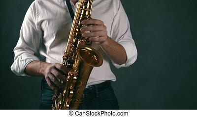 Medium shot of musician playing saxophone in studio. Real time.