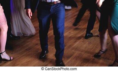 Medium shot of People are dancing on the dance floor in the nightclub.