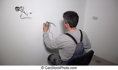 Medium shot of professional electrician doing socket repair....