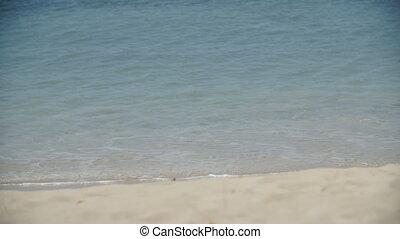 Medium shot of waves washing across the beach