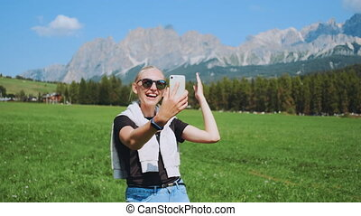 Medium shot of woman making video call from beautiful nature park in front of mountains. She sharing impressions from her trip.