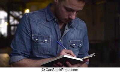 Medium shot of young handsome gay man writing on notepad in a big dark hall
