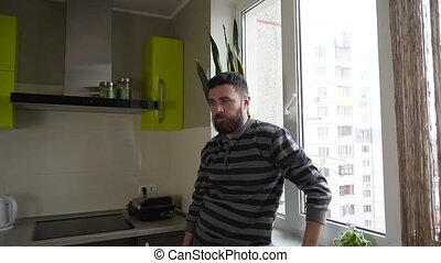 Medium shot of young man yawn next to the window in the kitchen