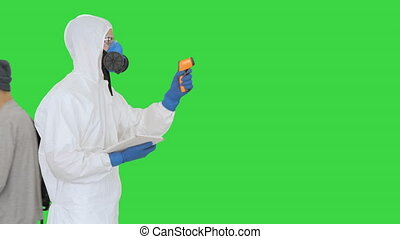 Operator check fever by digital thermometer on a Green Screen, Chroma Key.