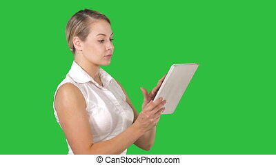 Pretty woman standing and using a tablet on a Green Screen,...