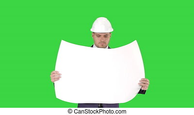 Professional architect is walking and holding blueprint The man is wearing helmet on a Green Screen, Chroma Key.